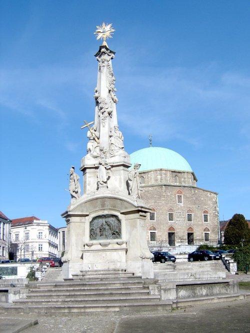 A piactéren 1717-től  állt Szentháromság-szobor. A jelenlegi a harmadik 1908-ból.  A háttérben a Gyertyszentelő Nagyboldogasszony templom, 1780-tól a város plébániatemploma.